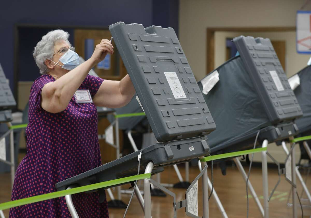 Kathy Trahan wears a facemask as she sets up voting stations before the polls open at the South Montgomery County Community Center, Thursday, July 2, 2020, in The Woodlands. Montgomery County commissioners will meet Monday to consider adding two early voting sites to help ease long lines as the county is on pace to surpass totals from the 2016 general election.