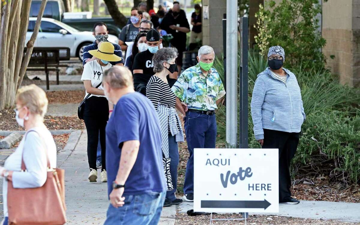 Voters wait in a line which extends around the far side of the building as Trish DeBerry, Republican candidate for commissioners court, greets supporters and others visiting the polls at Brookhollow Library on Oct. 14, 2020.