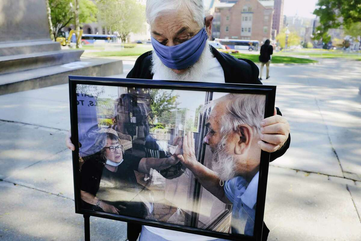 Robert Stanton, 80, holds a photo from this past May 13th that shows him visiting his wife, Carol, 79, at Teresian House on their 60th wedding anniversary, on Wednesday, Oct. 14, 2020, in Albany, N.Y. Robert came to the Capitol on Wednesday to take part in a protest against Governor Andrew M. Cuomo's policies that protesters say are preventing them from visiting loved ones in nursing homes. Stanton has only been able to get one visit with his wife, sitting twelve feet apart, back in August. Because visits have to be scheduled through the facility, the family's next visit with Carol is on November 25th. Tina Brooker, Robert and Carol's daughter, said that before Covid she would visit her mom and provide care for her in the facility four times a week, and she wants essential caregivers to have access to their loved one's room.