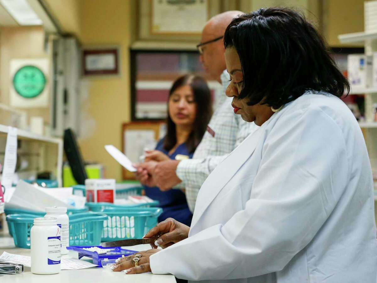 Dr. Anjanette Wyatt, right, fills prescriptions for clients inside Clinical Care Pharmacy on Wednesday, March 4, 2020, in Houston. Seven years ago, the state handed control of its Medicaid prescription drug program to private health plans in hopes of saving costs without sacrificing access to care. But the state has struggled to see any real savings, and doctors and pharmacists say the system has become increasingly confusing to navigate.