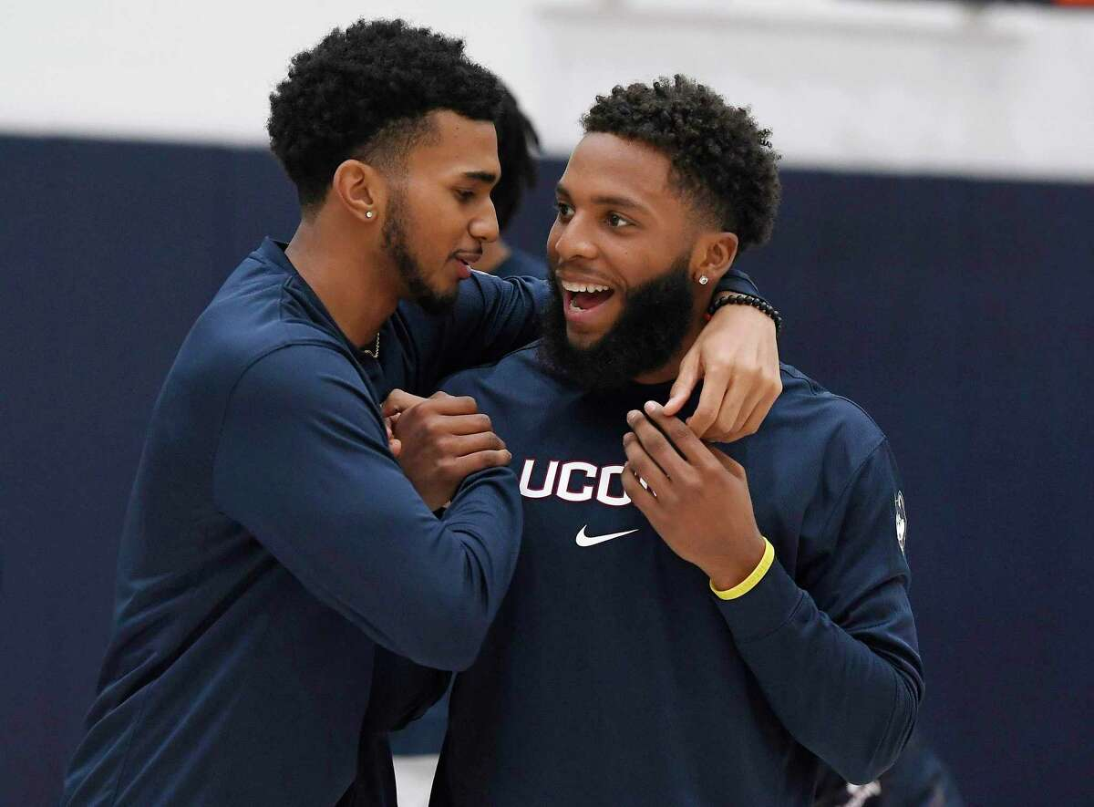 Connecticut's Jalen Gaffney, left, and R.J. Cole, right, share a moment on the practice court before UConn's men's and women's basketball teams' annual First Night celebration in Storrs, Conn. (AP Photo/Jessica Hill)