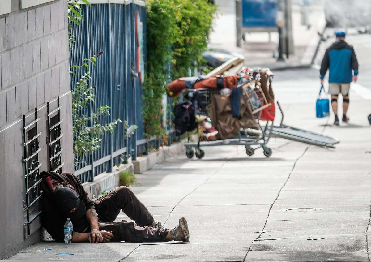 A man lies, passed out after getting high on a sidewalk near City Hall in San Francisco.