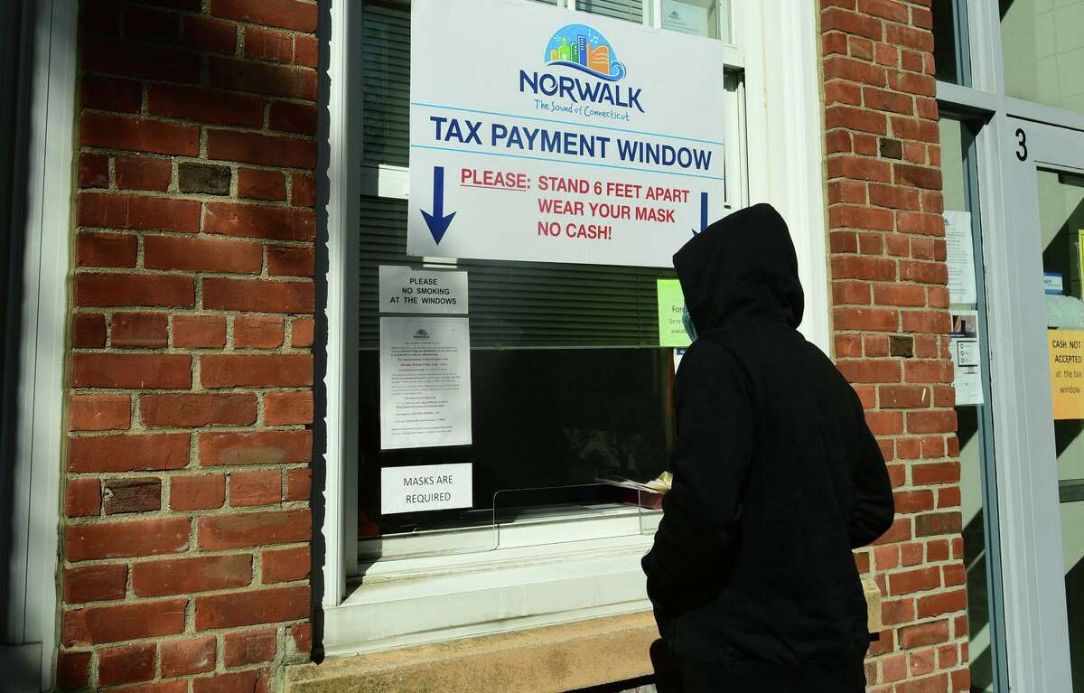 Residents use the walk-up window at the City of Norwalk Tax Office on October 14, 2020.