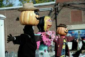 Scarecrows with pumpkin heads wait to be judged in front of the United Methodist Church in Bethel during the Bethel Chamber of Commerce annual Trick or Treat Street Halloween Bash, in downtown Bethel, Conn, on Saturday, October 25, 2014. The scarecrows are part of a fundraiser for the church which is raising funds to renovate the church, trick of treaters were given tickets to drop in buckets to vote for their favorite.