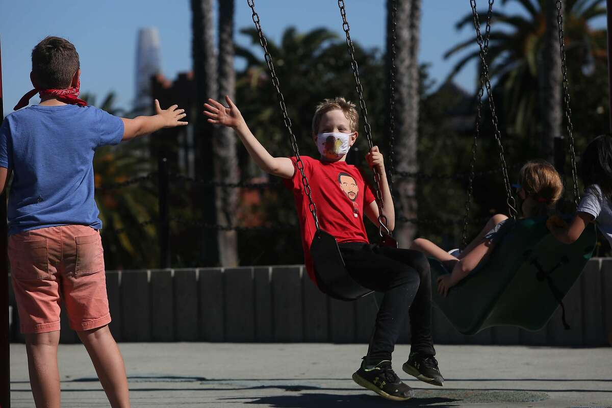 Desi Ach (l to r), 10 and Matty Taylor, 10, high five each other as Taylor swings and Ach watches at Hellen Diller playground in Dolores Park on October 14, 2020 in San Francisco.