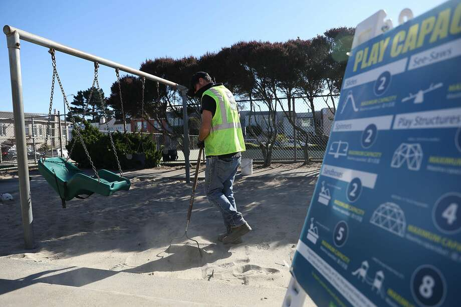 Gardener David Wallace rakes a sandbox at Miraloma Playground. San Francisco playgrounds, which have been closed since March, have reopened with time limits and restrictions on capacity. Photo: Lea Suzuki / The Chronicle