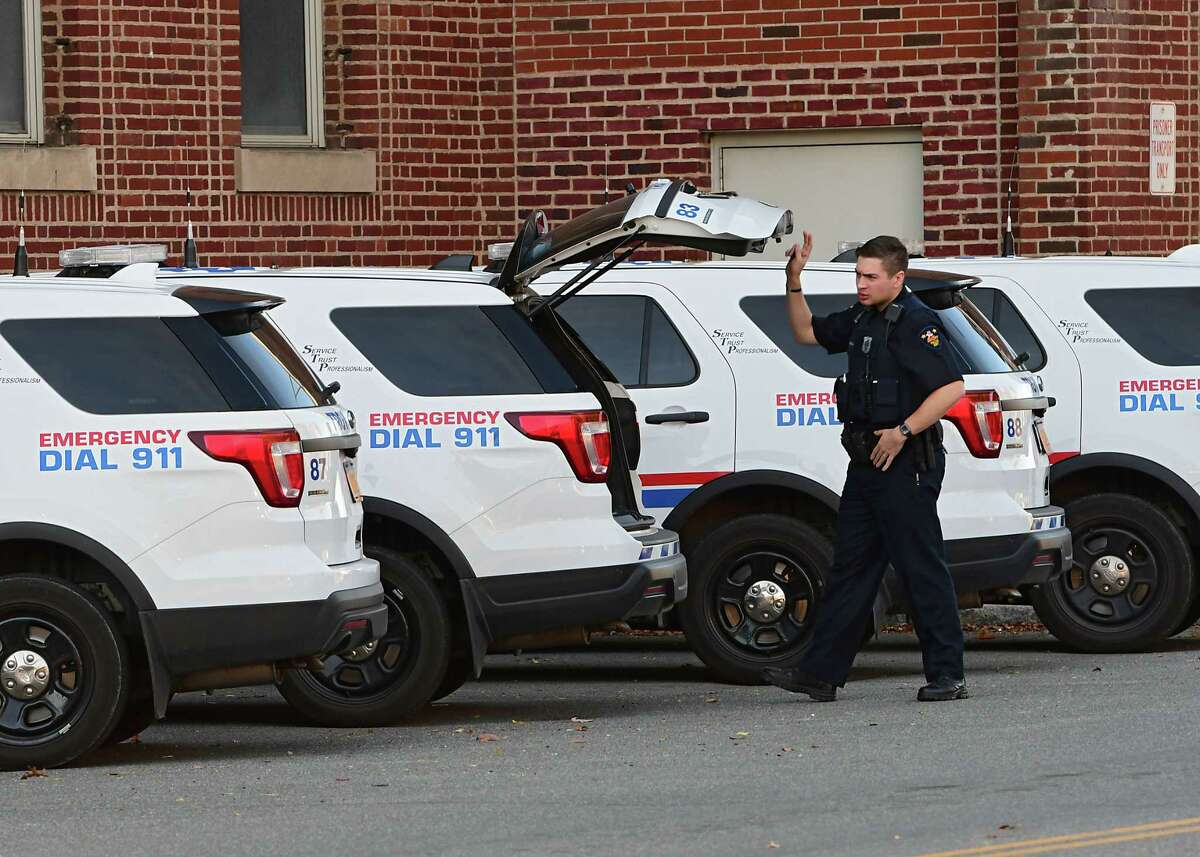 A police officer is seen closing the back of a police car parked outside the Troy Police Station on Wednesday, Oct. 14, 2020 in Troy, N.Y. Troy police are investigating a shooting that injured someone on March 8, 2021. (Lori Van Buren/Times Union)