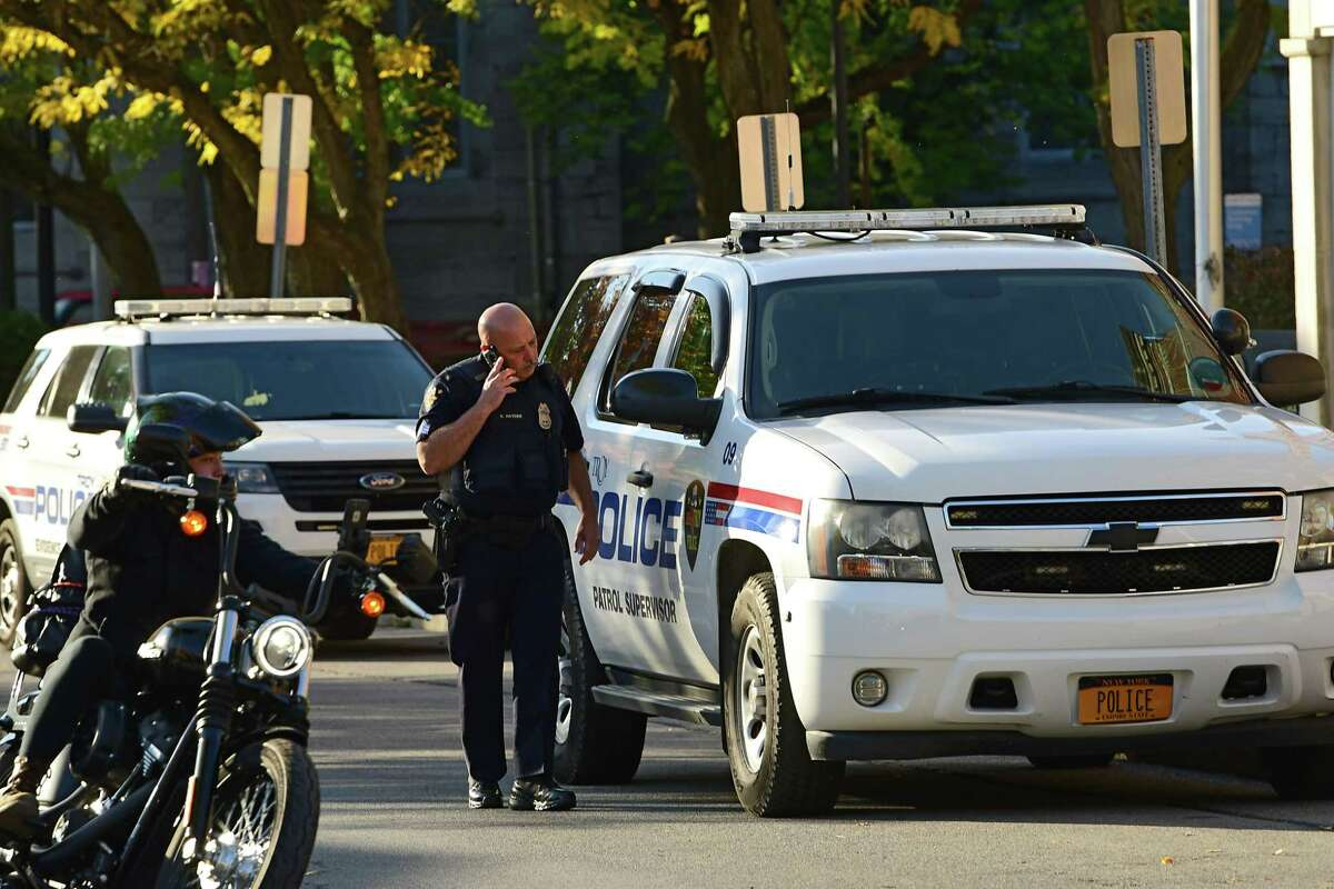 A police officer is seen on his phone outside the Troy Police Station on Wednesday, Oct. 14, 2020 in Troy, N.Y. (Lori Van Buren/Times Union)
