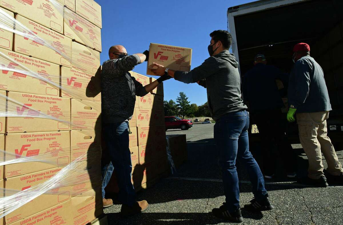 Volunteers load a truck to distribute food under the U.S. Department of Agriculture's Farmers to Families Food Boxes program on Thursday, Oct. 8, 2020, in Norwalk, Conn.