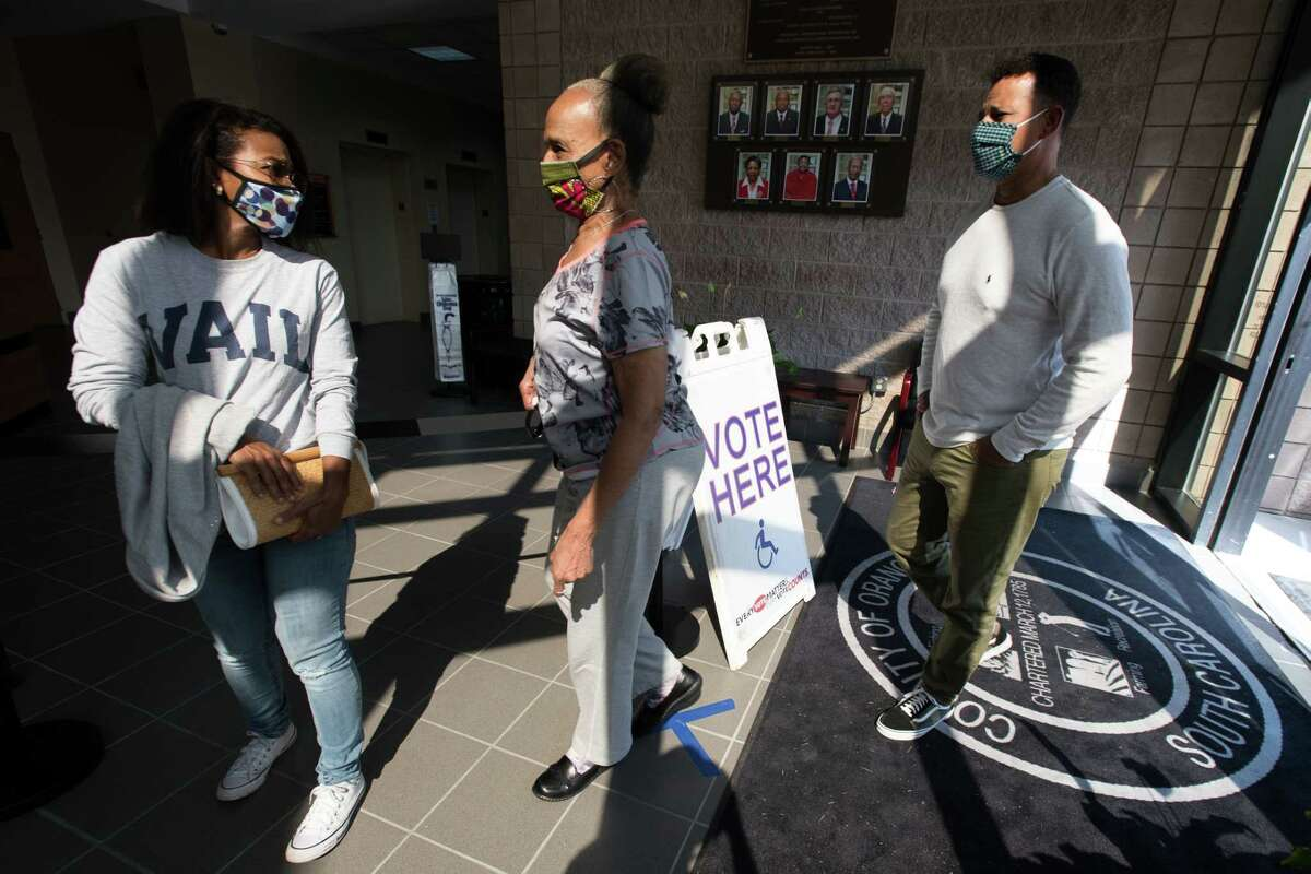 Kimberly Roache, left, Geneva Roache and Martin Roache stand in line to cast ballots at the Richland County Voter Registration and Elections Office in Columbia, S.C., on the first day of in-person absentee voting Monday, Oct. 5, 2020.