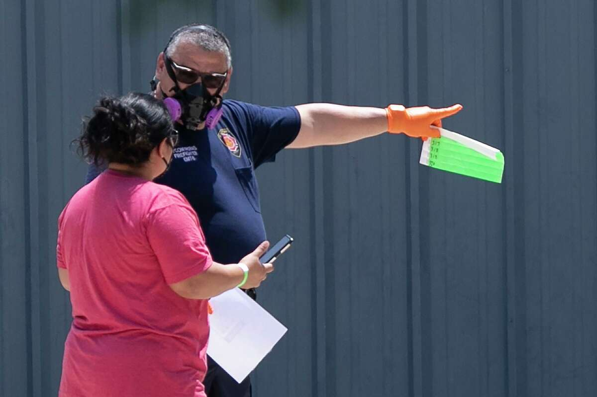 A firefighter directs a woman to a Metro Health COVID-19 walk-up testing site in July. A reader says it's time for Metro Health to get its act together on data collection.