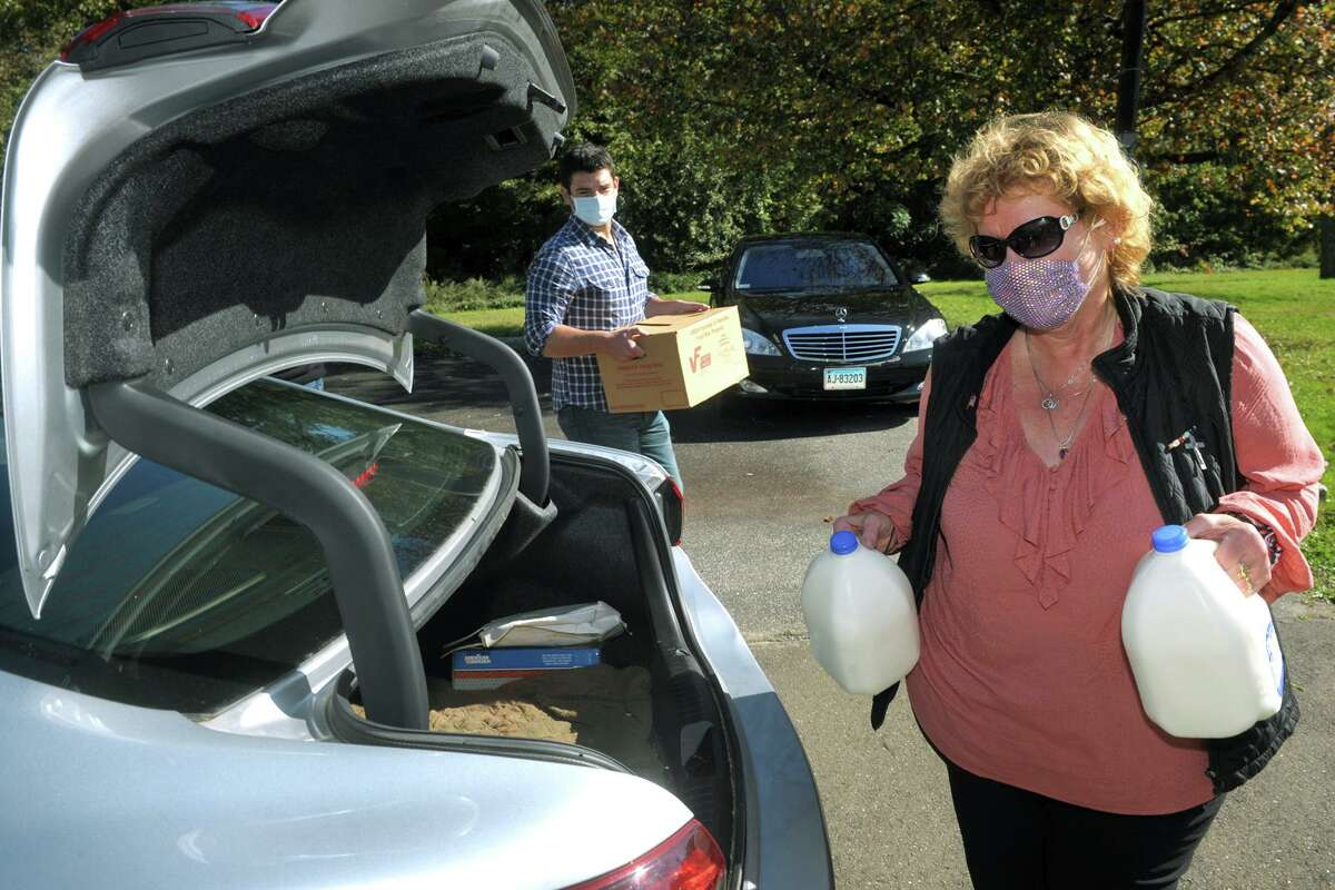 Linda Frame and Stephen Del Vecchio carry milk and boxed groceries to the trunk of a waiting car during the Ansonia's annual Senior Health Fair at Warsaw Park, in Ansonia, Conn. Oct. 14, 2020. This year's fair was a drive through event.