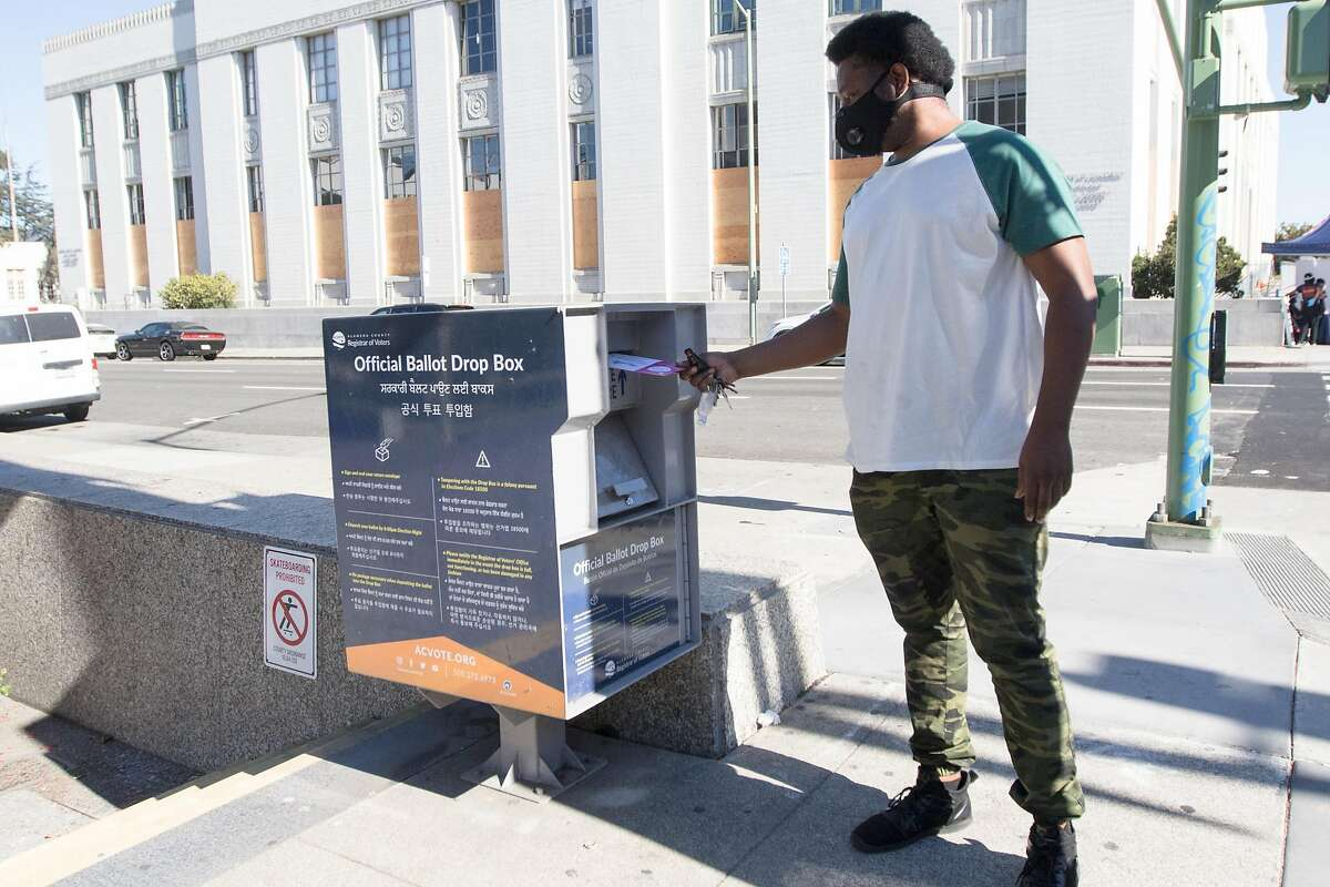 A voter drops off their ballot in an official Alameda County Registrar of Voters drop box across the street from the Alameda County Courthouse in Oakland, Calif., on Oct. 14, 2020.