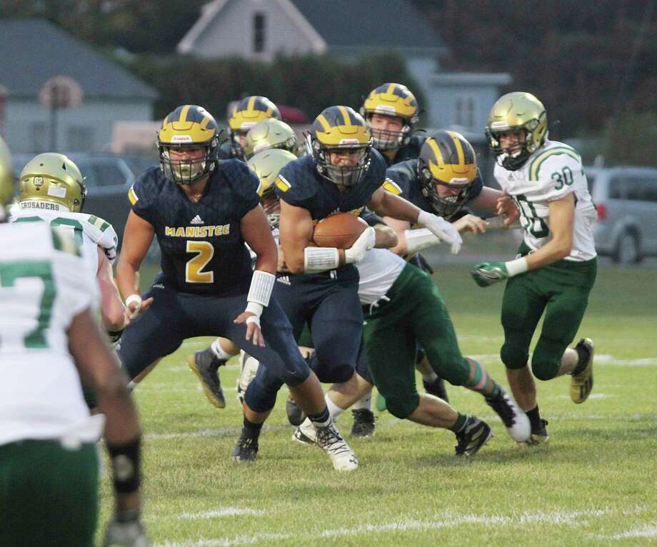 Manistee's Brady Mikula (2) looks to block for running back Landen Powers during the Chippewas' loss to Muskegon Catholic Central last week. (News Advocate file photo)