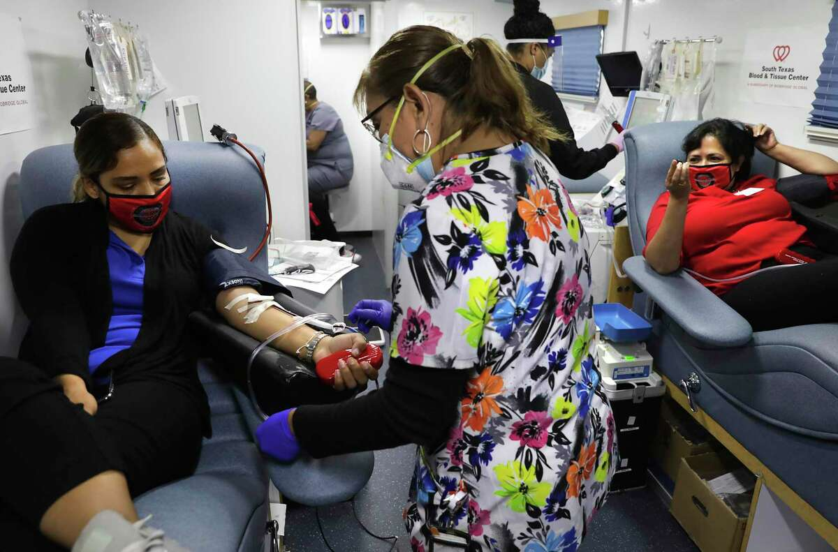 Rosie Hernandez, center, prepares Virginia Martinez, left, to donate plasma, as Barbara Silva, right waits. WestCare Texas has partnered with South Texas Blood and Tissue Center for a Convalescent Plasma drive at Ella Austin Community Center, on Wednesday, Oct. 14, 2020.
