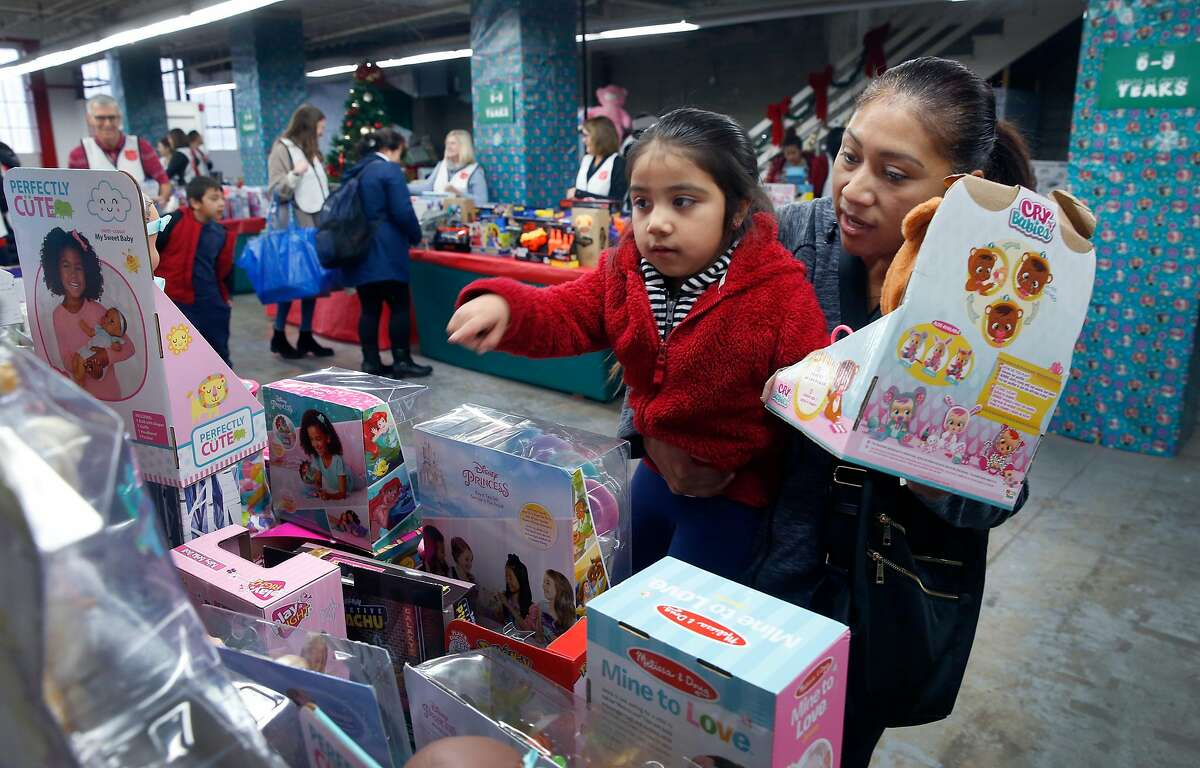 """Lorena Lopez chooses a doll with her daughter Leslie, 6, at the Salvation Army's holiday Toy & Joy Shop in San Francisco, Calif. on Wednesday, Dec. 18, 2019. More than 1,500 pre-registered families were able to choose free toys for the holiday season in a """"retail-like"""" experience and were assisted by dozens of volunteers."""
