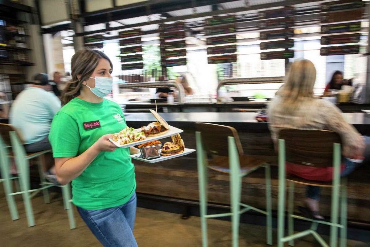 Server BayLeah Burton brings food to a table at Muck & Fuss Craft Beer and Burger Bar in New Braunfels, Texas on Friday, Sept. 18, 2020. Gov. Greg Abbott eased up statewide coronavirus restrictions on Thursday, allowing restaurants, retail stores and office buildings now at 50% capacity to expand to 75% capacity beginning Monday. (Mikala Compton/Herald-Zeitung via AP)