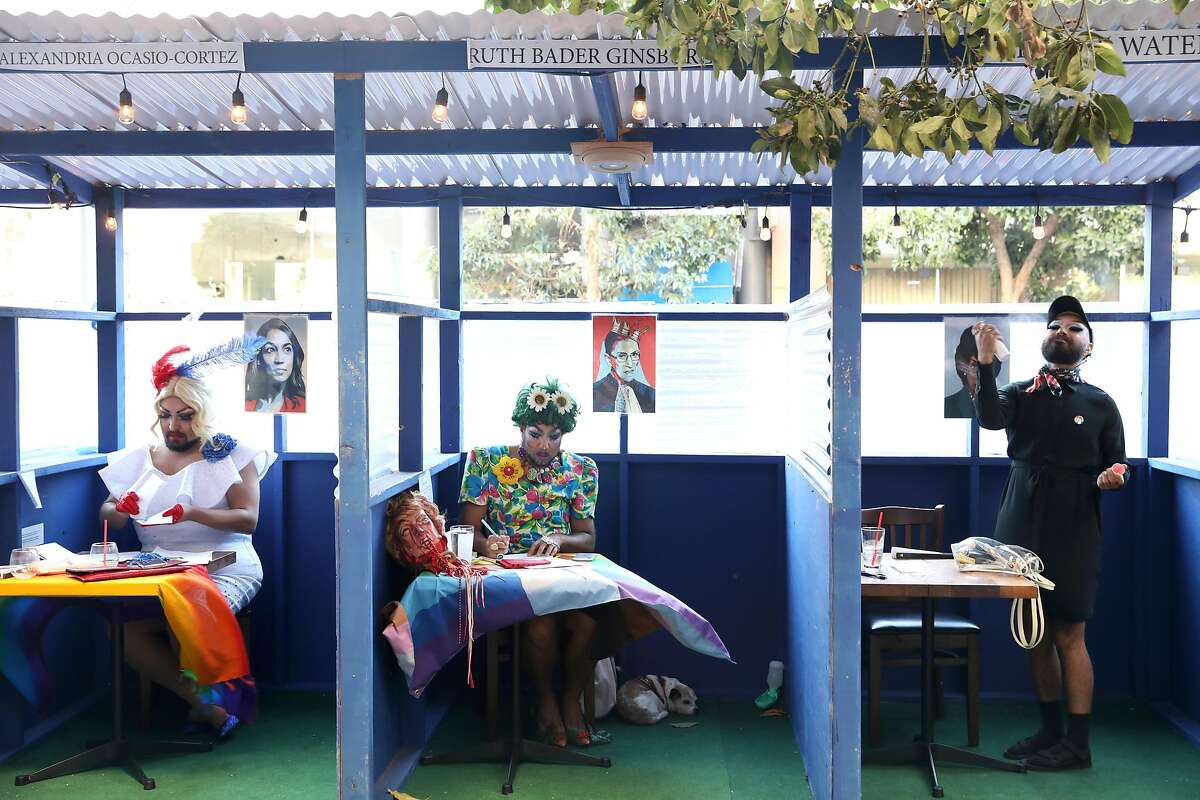 Foxxy Blue Snacks (left) and Trangela Lansbury (middle) and Grace Towers (right) in the outside booths at Manny's as they participate in an election event writing letters to swing state voters on Tuesday, Oct. 13, 2020, in San Francisco, Calif.
