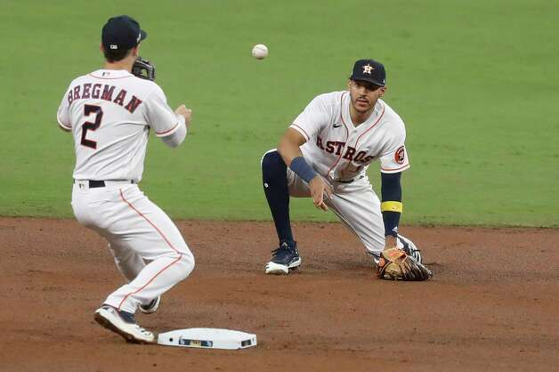 Houston Astros Carlos Correa (1) flips the ball to Alex Bregman (2) as they turn a double play on a grounder by Tampa Bay Rays Yoshi Tsutsugo during the third inning of Game 4 of the American League Championship Series at Petco Park Wednesday, Oct. 14, 2020, in San Diego. Photo: Karen Warren, Staff Photographer / © 2020 Houston Chronicle