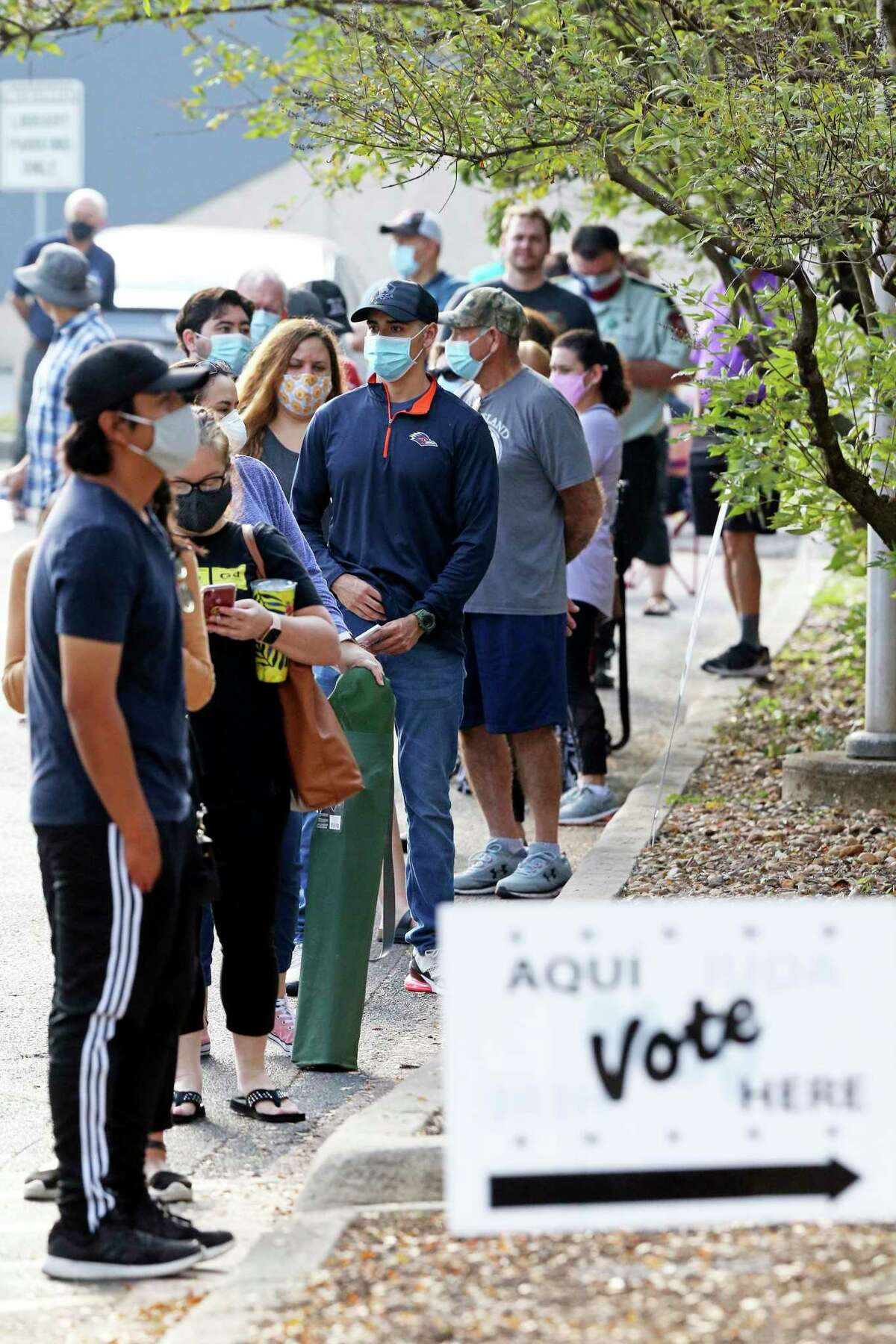 Voters wait in a line at the Brookhollow Library early voting site.