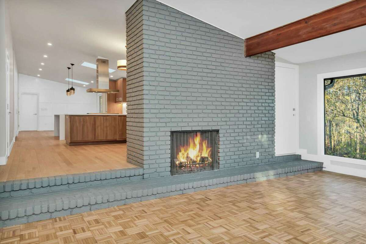 At 34 Montgomery Lane, the kitchen steps down to the expansive living room, with a wood-burning fireplace, beamed ceiling, nearly an entire wall of windows, and a period-appropriate parquet floor.