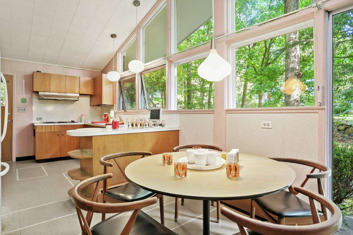 The kitchen and breakfast room at 261 Cognewaugh have a bright perspective, with oversized windows looking out to a canopy of trees.