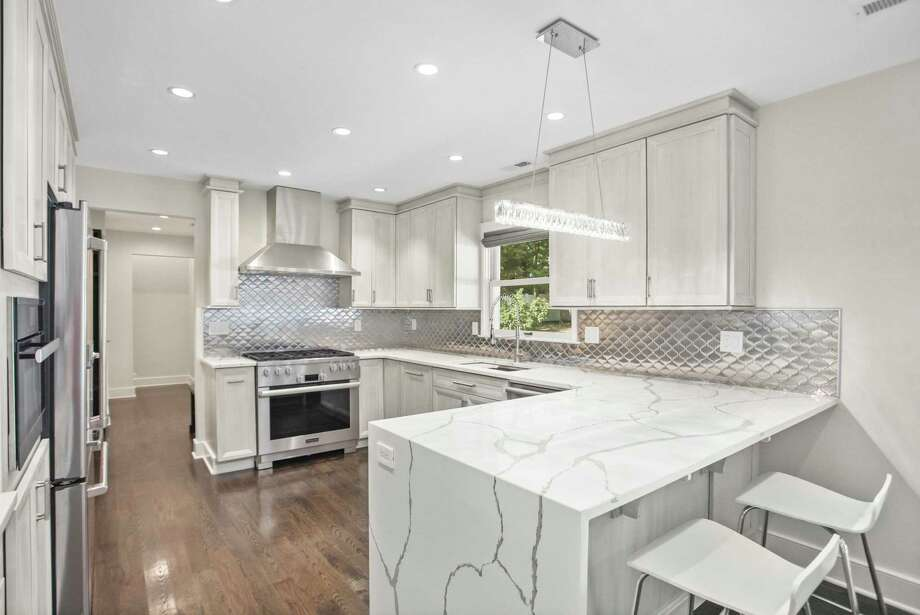 """The kitchen was designed to """"maximize functionality,"""" according to the seller, who selected Miele appliances and Calacatta Gold surfaces for the remodel. Photo: Sotheby's International Realty / Contributed Photo"""