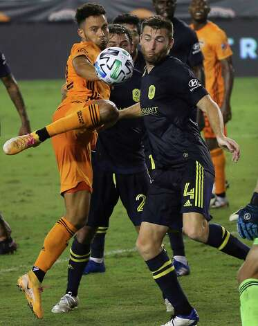 Houston Dynamo forward Niko Hansen (12) tries to score a goal with a corner kick while Nashville SC defender David Romney (4) is trying to stop him during the second half of a MLS game Wednesday, Oct. 14, 2020, at BBVA Stadium in Houston. Houston Dynamo lost to Nashville SC 3-1. Photo: Yi-Chin Lee, Staff Photographer / © 2020 Houston Chronicle