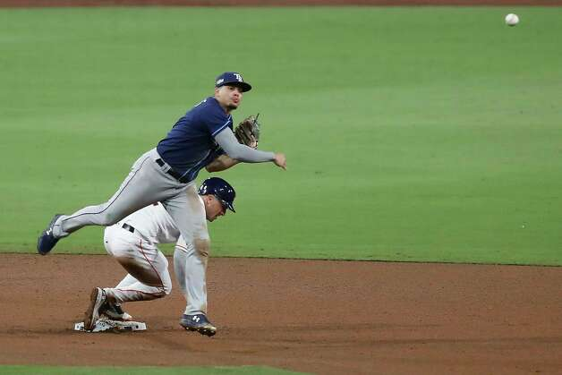 Tampa Bay Rays Willy Adames throws over Houston Astros Alex Bregman as he turns a double play on a grounder by Carlos Correa to end the eighth inning of Game 4 of the American League Championship Series at Petco Park Wednesday, Oct. 14, 2020, in San Diego. Photo: Karen Warren, Staff Photographer / © 2020 Houston Chronicle