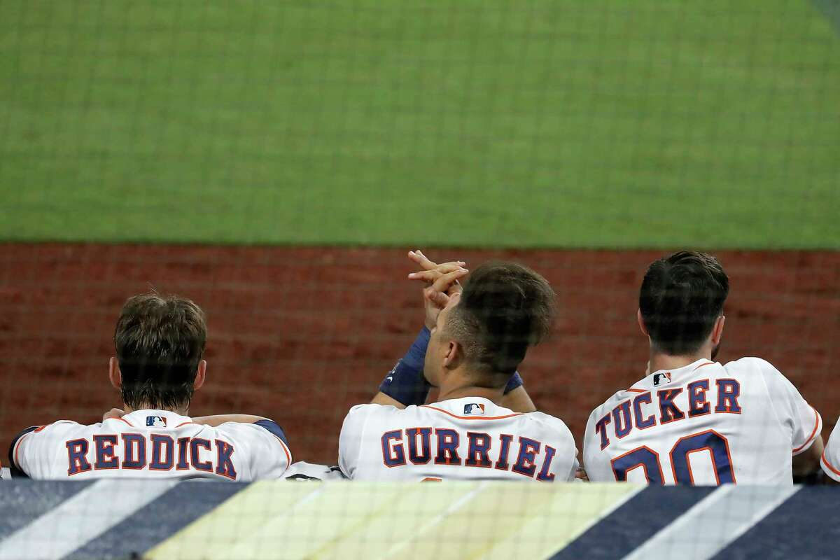 Houston Astros Josh Reddick (22), Yuli Gurriel (10) and Kyle Tucker (30) look on from the dugout during Game 4 of the American League Championship Series against the Tampa Bay Rays at Petco Park Wednesday, Oct. 14, 2020, in San Diego.