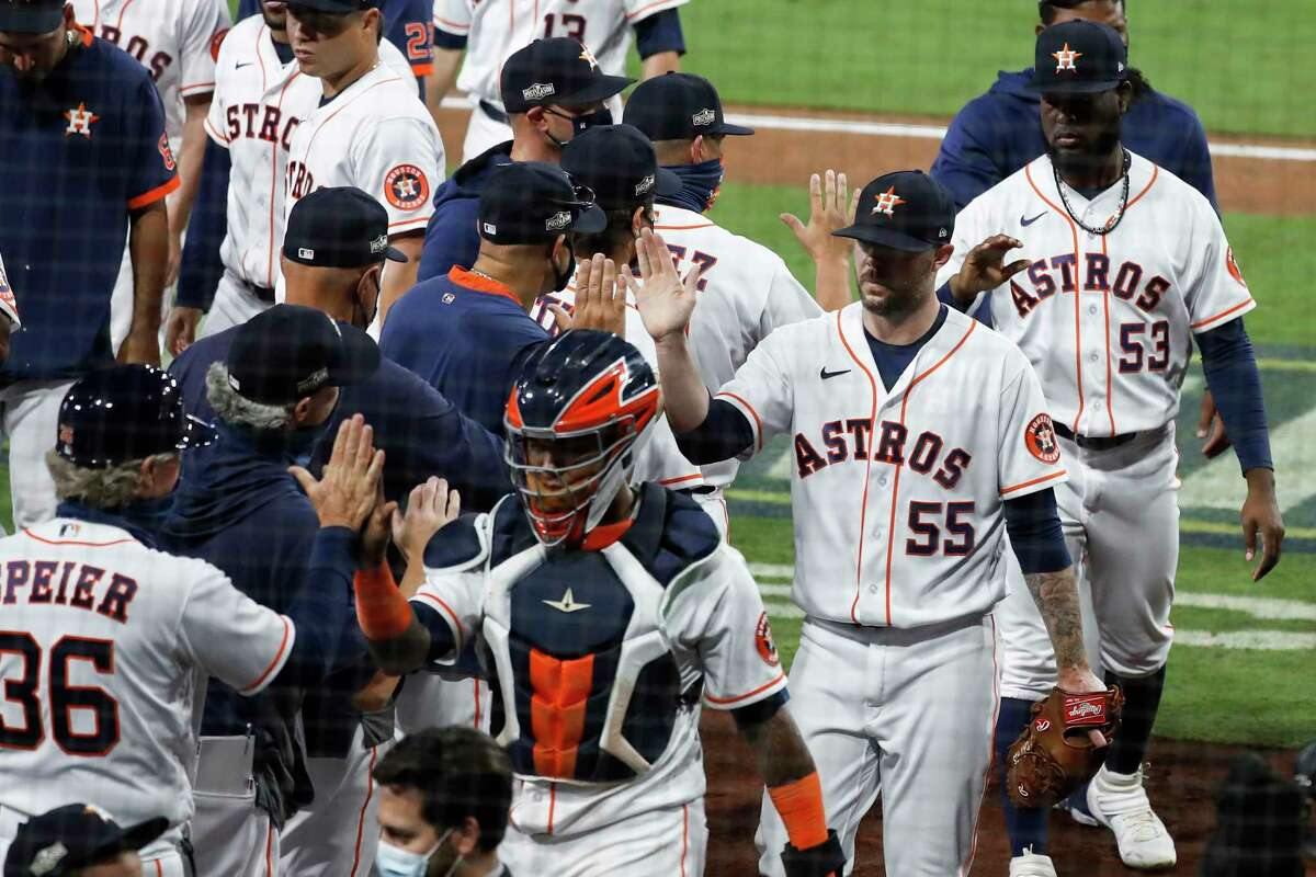 Houston Astros Ryan Pressly (55) high fives his teammates after closing out the Tampa Bay Rays to hold onto a 4-3 win to stay alive in the American League Championship Series at Petco Park Wednesday, Oct. 14, 2020, in San Diego. The Rays lead the best-of-seven series 3-1.
