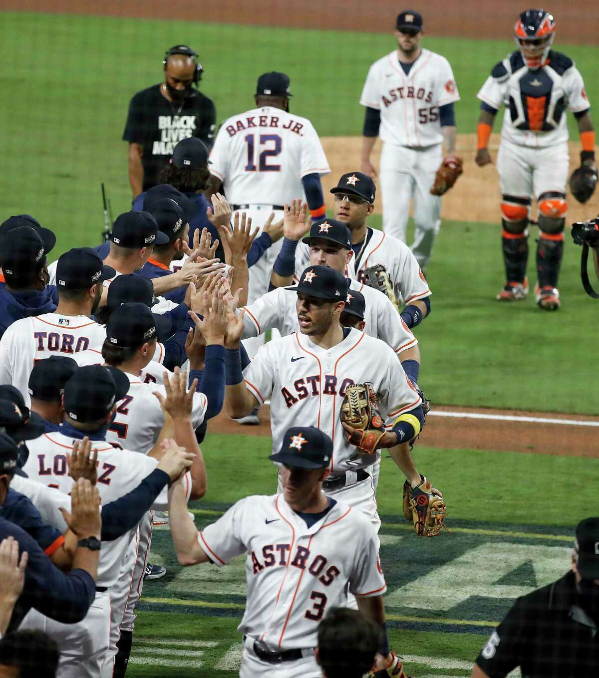 Houston Astros players high five after the Astros beat the Tampa Bay Rays 4-3 to stay alive in the American League Championship Series at Petco Park Wednesday, Oct. 14, 2020, in San Diego. The Rays lead the best-of-seven series 3-1.