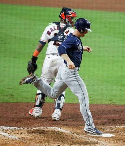 Tampa Bay Rays Joey Wendle touches home as he runs past Houston Astros Martin Maldonado (15) to score on an RBI double by Willy Adames during the ninth inning of Game 4 of the American League Championship Series at Petco Park Wednesday, Oct. 14, 2020, in San Diego. Photo: Karen Warren, Staff Photographer / © 2020 Houston Chronicle