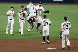 Houston Astros Carlos Correa (1) and George Springer (4) leap in the air to high five after the Astros beat the Tampa Bay Rays 4-3 to stay alive in the American League Championship Series at Petco Park Wednesday, Oct. 14, 2020, in San Diego. The Rays lead the best-of-seven series 3-1.