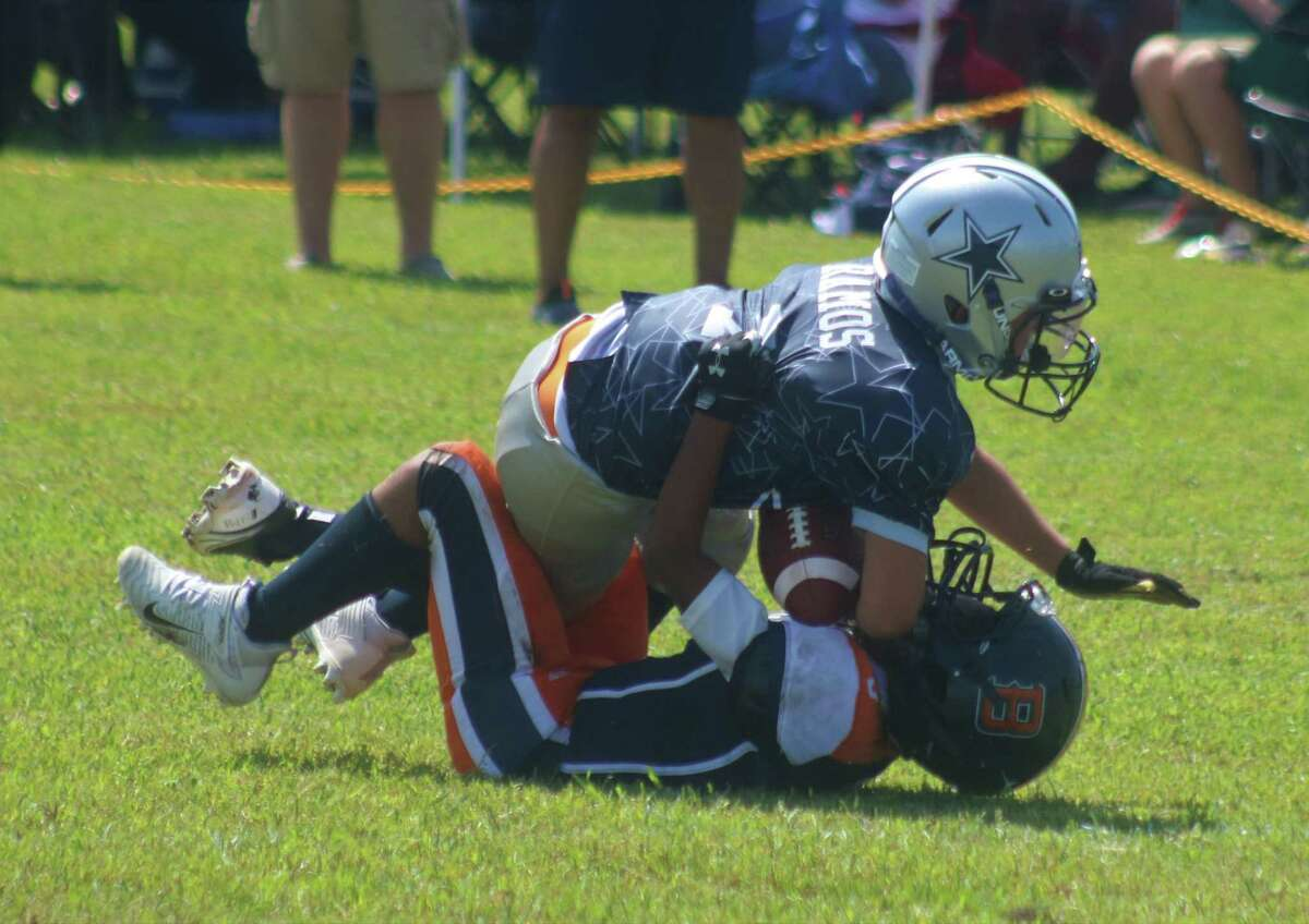 A League City Junior Cowboy ballcarrier is pulled down to the ground by a Baytown Bronco during Week 3 action. The Junior squad is 3-2 at the halfway mark, hoping to earn a TIFI playoff berth in the upcoming weeks.
