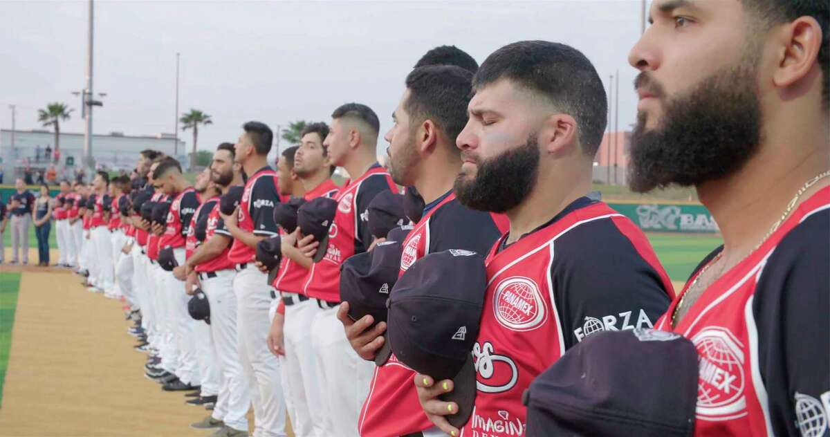 Luis Flores (second fro right) and members of the Tecolotes de los Dos Laredo, a binational professional baseball team with home stadiums in Nuevo Laredo, Mexico, and Laredo, Texas, stand for the U.S. National Anthem before a game in 2019 in Laredo in a scene from