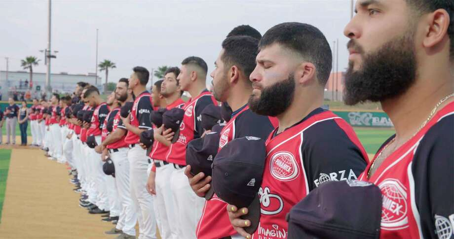 """Luis Flores (second fro right) and membersof the Tecolotes de los Dos Laredo, a binational professional baseball team with home stadiums in Nuevo Laredo, Mexico, and Laredo, Texas, stand for the U.S. National Anthem before a game in 2019 in Laredo in a scene from """"Bad Hombres."""" The Showtime documentary follows this Mexican League baseball team that plays on both sides of the U.S.-Mexico border amid the tension around migration, divisive politics, and environmental concerns. Photo: AP / Copyright 2020 The Associated Press. All rights reserved."""