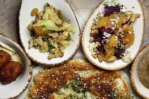 The mezze plates menu at Jardin include, clockwise from bottom, fresh-baked pita, Bolognese-stuffed arancini, Sicilian cauliflower, roasted beets and baba ganoush.