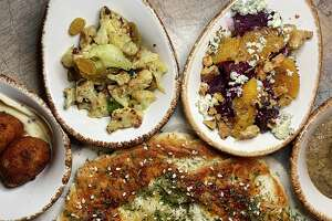 The mezze plates menu at Jardin include, clockwise from bottom, fresh-baked pita, Bolognese-stuffed arancini, Sicilian cauliflower, roasted beets and baba ganoush.