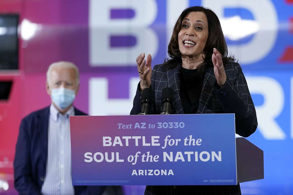 In this Oct. 8, 2020, photo, Democratic vice presidential candidate Sen. Kamala Harris, D-Calif., speaks at Carpenters Local Union 1912 in Phoenix, as Democratic presidential candidate former vice president Joe Biden listens. Biden's presidential campaign says Harris will suspend in-person events until Oct. 19, after two people associated with the campaign tested positive for coronavirus. (AP Photo/Carolyn Kaster)