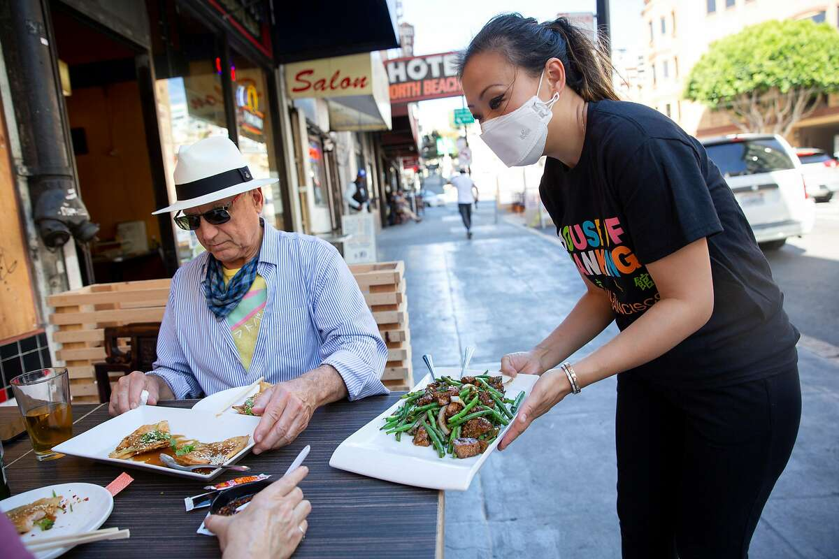 Kathy Fang brings food to customers dining outdoors at House of Nanking restaurant in San Francisco.