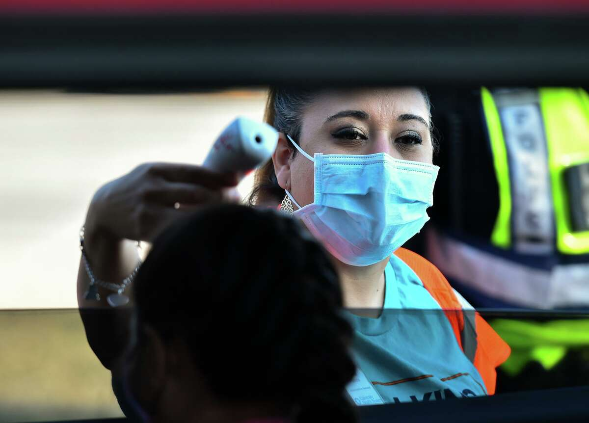 Pamela Reyes checks temperatures as people arrive during a drive-thru flu shot event at Nelson Wolff Stadium on Saturday.