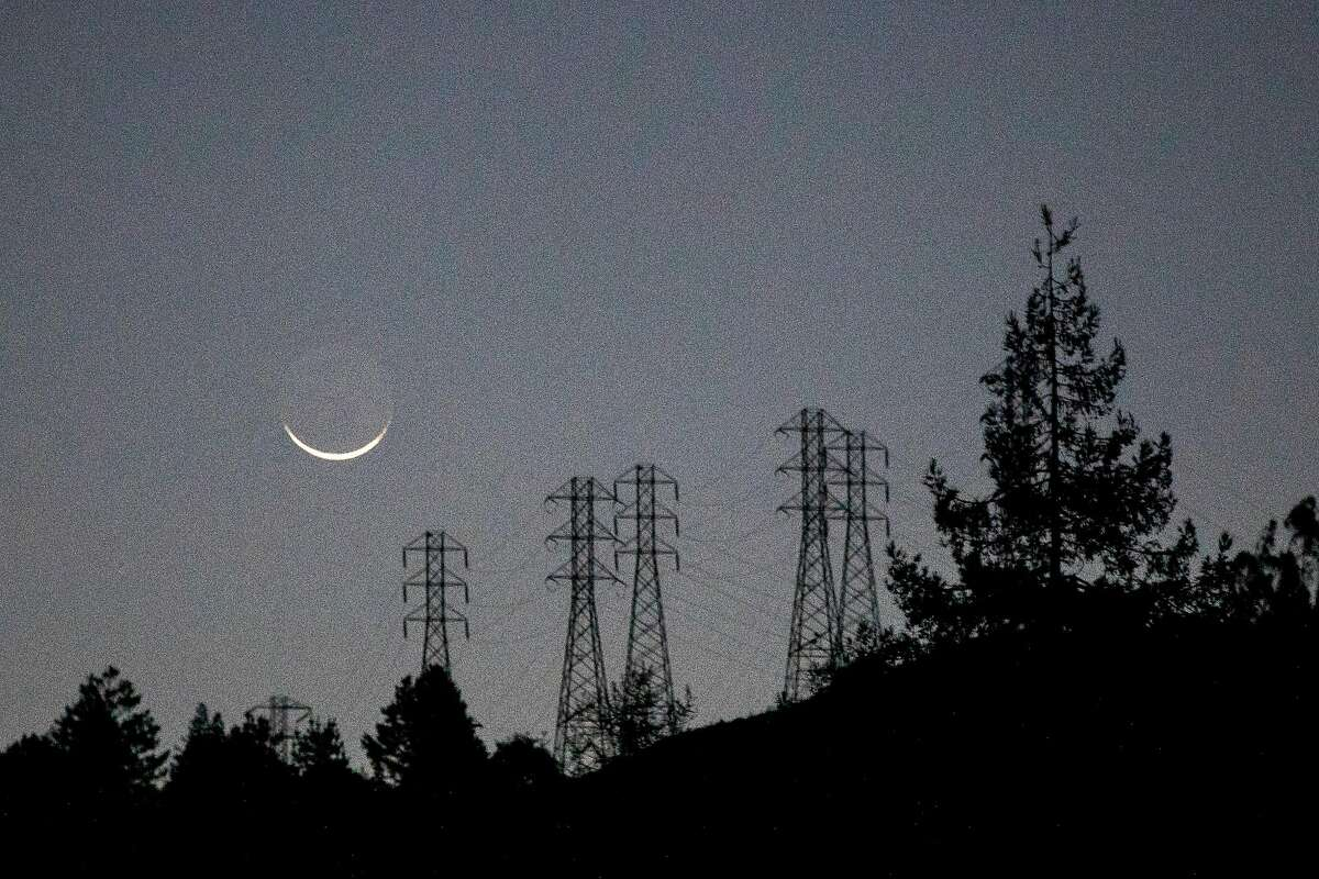 A sliver moon sets over a darkened hillside and PG&E high-voltage power lines seen from Highway 24 in Oakland.