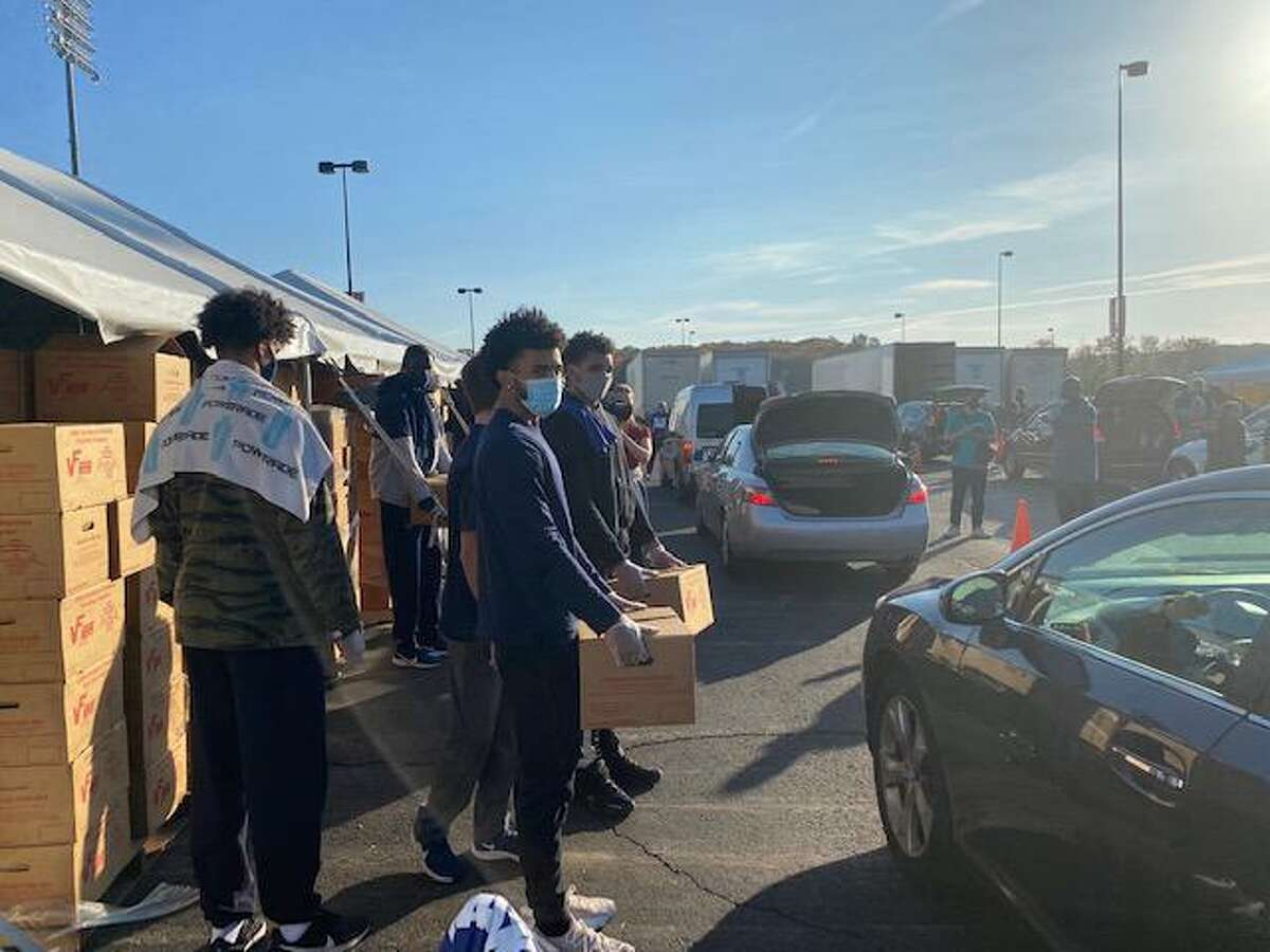 UConn men's basketball players help distribute groceries at a Foodshare-sponsored food drive on Thursday morning at Rentschler Field.