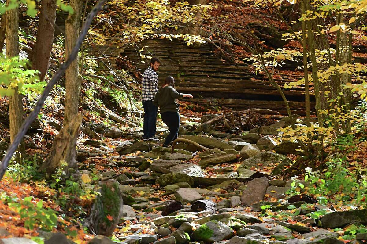 People walk in a dried up creek among the Fall foliage at John Boyd Thacher State Park on Thursday, Oct. 15, 2020 in New Scotland, N.Y. (Lori Van Buren/Times Union)