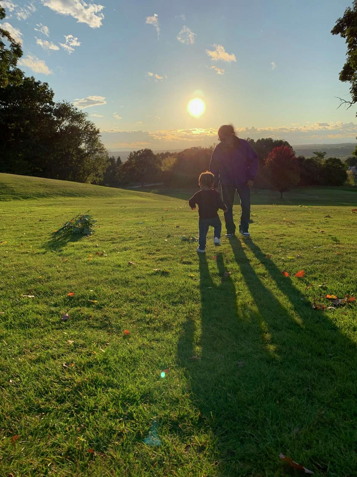 Troy resident Danyelle Hagan's son Bryson takes a late afternoon walk in Frear Park with his mom and his grandmother.
