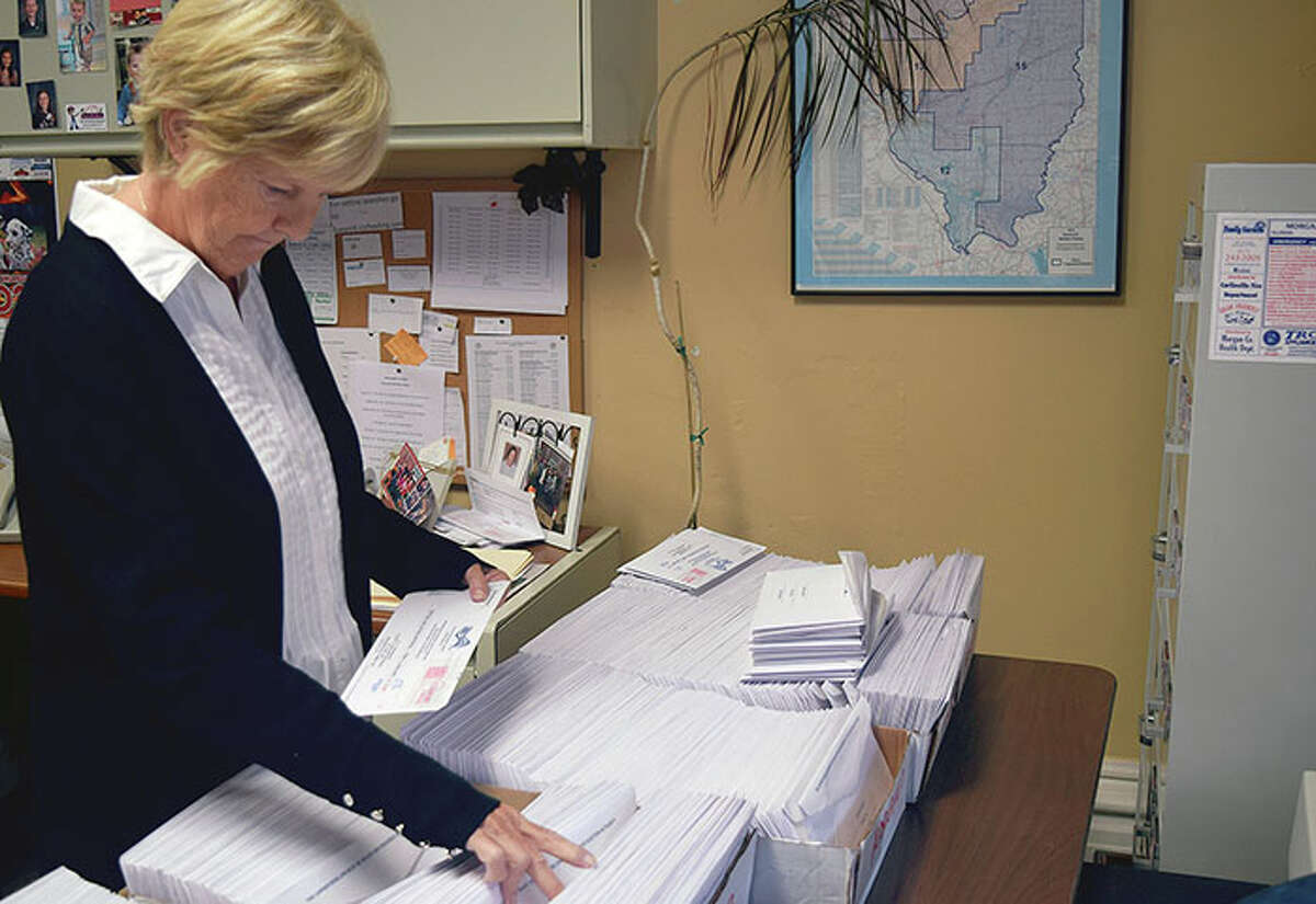 Joan Ryan, an election helper for Morgan County, prepares mail-in ballots at the Morgan County Courthouse.