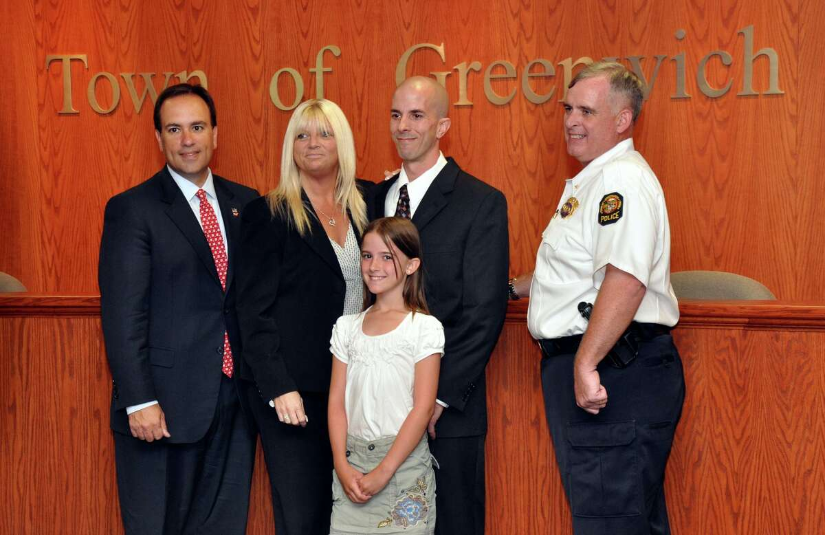 Bobbi Tar poses with her husband, John Tar, at his 2011 swearing-in ceremony as a Greenwich firefighter alongside their daughter Anni, First Selectman Peter Tesei, and Deputy Police Chief Jim Heavey.