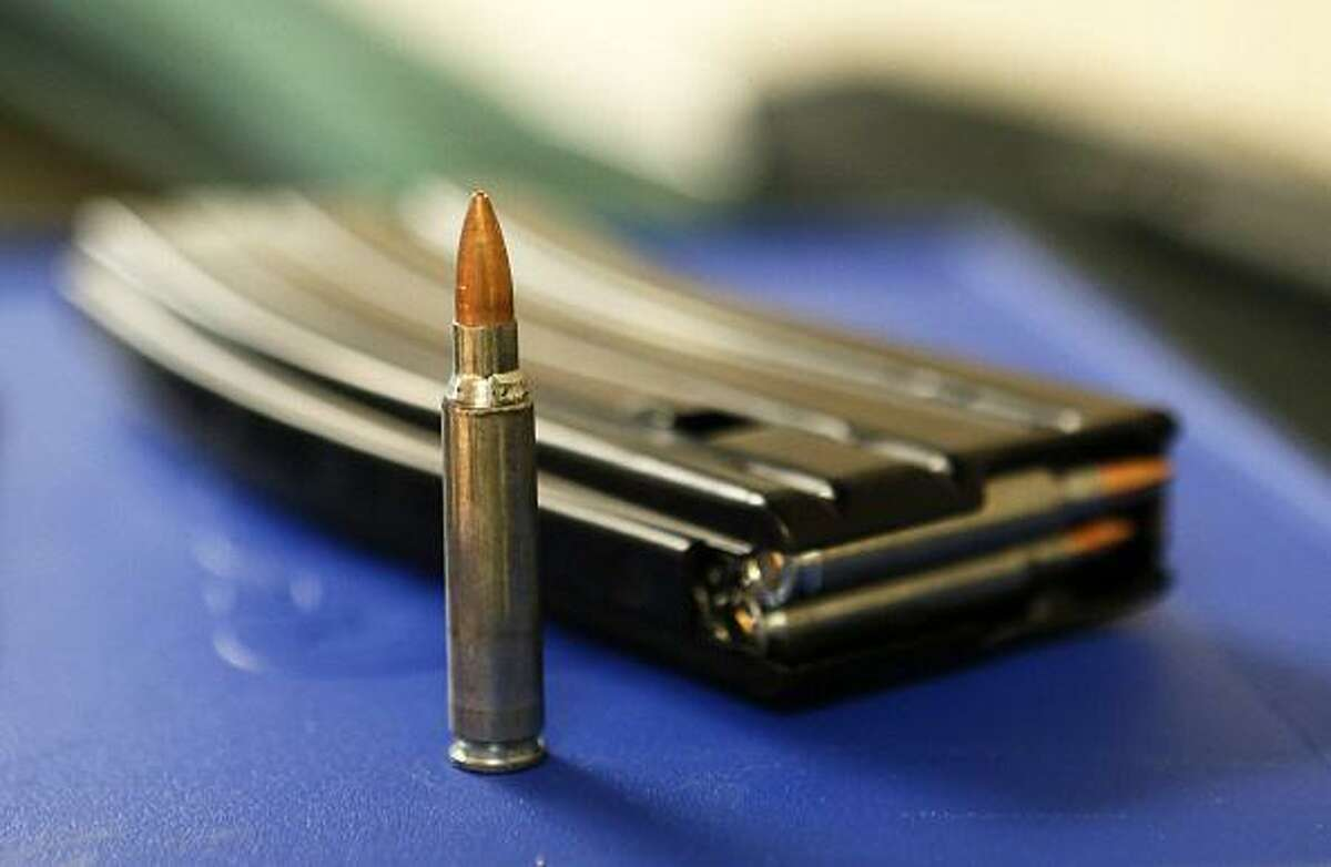 Shown is .223 AR-15 ammunition and a high capacity 30-round clip on a table at the