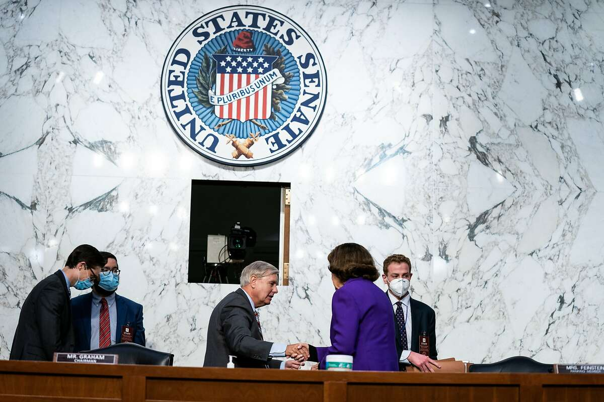 Senate Judiciary Committee Chairman Sen. Lindsey Graham, R-S.C., and California Democratic Sen. Dianne Feinstein shake hands after the end of the fourth day of confirmation hearings for Supreme Court nominee Amy Coney Barrett on Thursday.